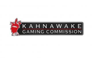 Czerwona głowa Indianina i biały napis KAHNAWAKE GAMING COMMISSION na ciemnoszarym tle i całość na białym tle