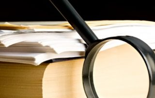 Czarna duża lupa oparta o stos papierów leżących na grubej książce z czarną okładką