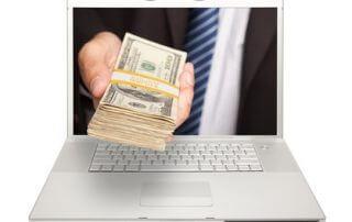 Ręka biznesmana wystaje z ekranu laptopa oferując dolary