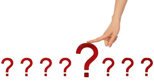 Palec wskazujący oparty na dużym czerwonym znaku zapytania w otoczeniu siedmiu mniejszych znaków zapytania