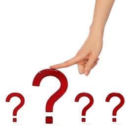 Palec wskazujący oparty na dużym czerwonym znaku zapytania w otoczeniu trzech mniejszych znaków zapytania