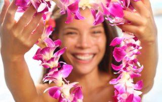 Uśmiechnięta brunetka patrzy na ciebie przez wyciągnięty przed siebie wieniec różowych kwiatów