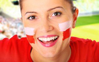 Twarz uśmiechniętej brunetki z pomalowanymi policzkami na biało czerwono na tle stadionu piłkarskiego