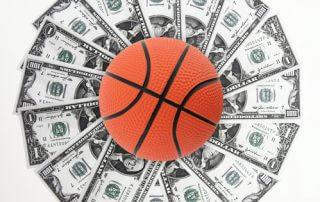 Piłka do koszykówki leży na wachlarzu z dolarów