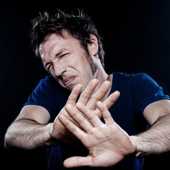 Brunet w ciemnym podkoszulku wzbrania się rękami z miną obrzydzenia na twarzy