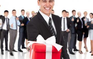 Pan w garniturze na tle pracowników daje czerwony prezent
