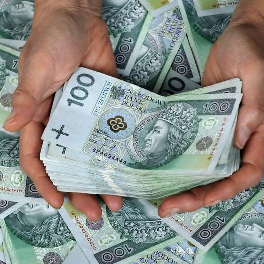 Plik banknotów stuzłotowych położony na dłoniach na tle wymieszanych banknotów stuzłotowych
