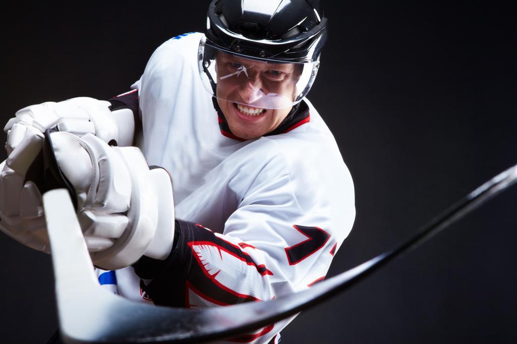 Hokeista w białym stroju zamachuje się w kierunku widza z zaciśniętymi zębami