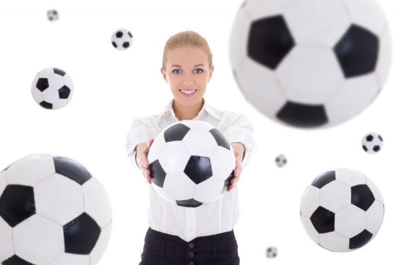 Uśmiechnięta kobieta w białej koszuli trzyma przed sobą piłkę nożną w otoczeniu wiszących piłek wokół