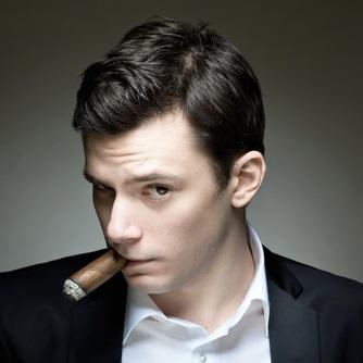 Mężczyzna w marynarce patrzący bokiem na widza z cygarem w ustach