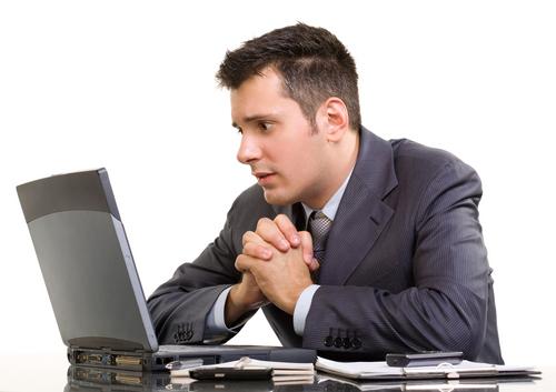 Mężczyzna siedzi wpatrzony w laptop ze splecionymi dłońmi w geście prośby i strachem w oczach