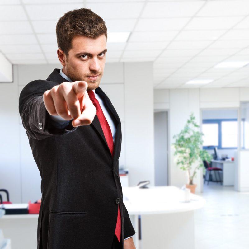 Mężczyzna w garniturze wskazuje na ciebie palcem z surową miną na tle biura firmy