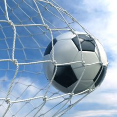 Piłka nożna w napiętej siatce bramki na tle nieba
