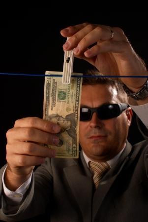 Mężczyzna w garniturze i ciemnych okularach wiesza na sznurku banknot dolarowy