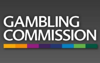 Biały napis GAMBLING COMMISSION z kolorowym paskiem jako podkreślenie na ciemno szarym tle
