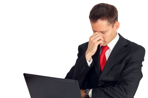 Mężczyzna w garniturze trzyma na kolanach laptop i chwyta się za nos ze spuszczoną głową