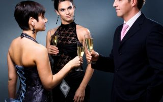 Biznesman z kieliszkiem szampana w otoczeniu dwóch pięknych kobiet