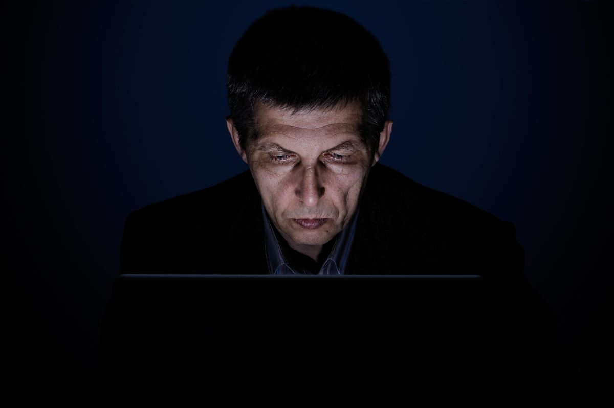 Podświetlona twarz mężczyzny w średnim wieku przed laptopem