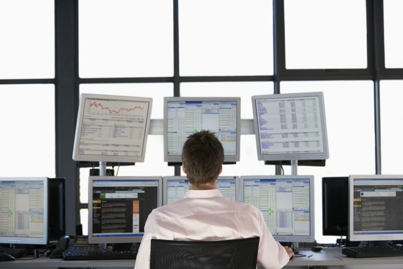 Mężczyzna w białej koszulki siedzi przed zestawem monitorów