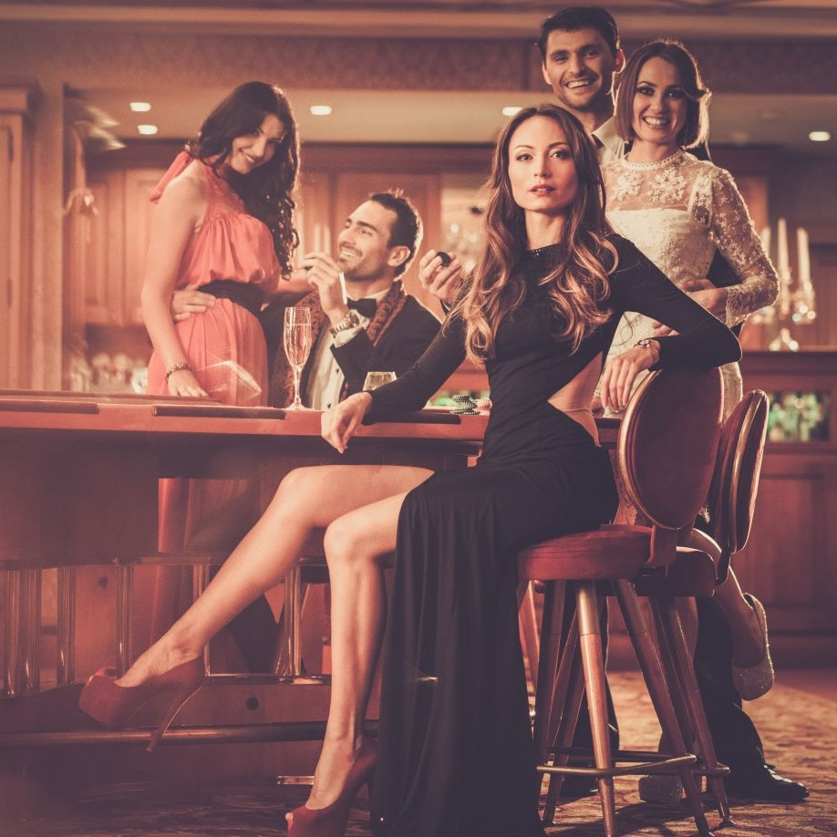 Atrakcyjna kobiet siedzi bokiem przy barze w czarnej sukience z odkrytymi nogami na tle radosnych osób