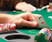 Ręka gracza otoczona żetonami do pokera pokazuje parę asów na zielonym stoliku